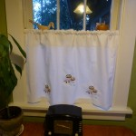 Close-up, craftsman style embroidered kitchen curtain